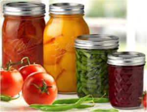 Home canned jars of green beans, peaches, and other foods with fresh tomatoes in foreground.