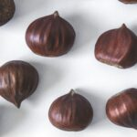 Image of chestnuts evenly spaced on a white border