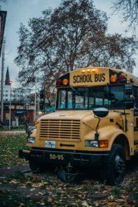 la foto es un autobús amarillo con arboles atras de el