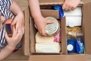 Hands adding food to donation box.